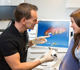 Dentist and patient consulting over CEREC crown technology
