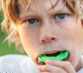 Teen placing green mouthguard