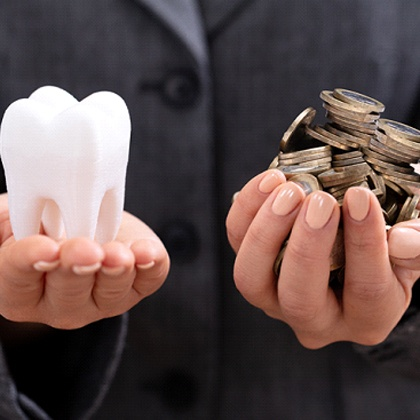 3D model of a tooth next to a handful of coins