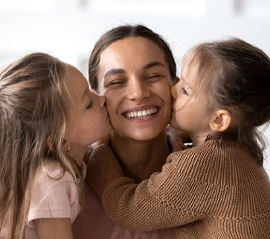 person with a dental bridge smiling as their children kiss either side of their cheeks