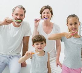 A family brushing their teeth together