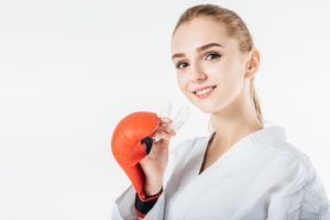 Woman with boxing glove holding a mouthguard